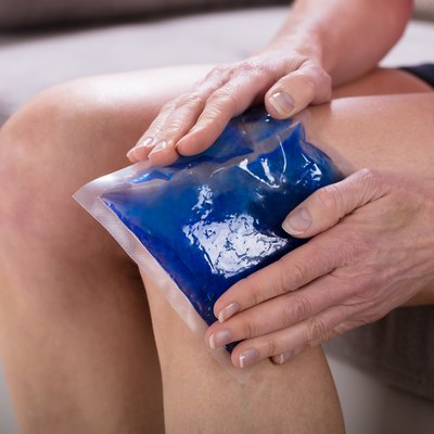 Woman Applying Ice Bag On Her Knee