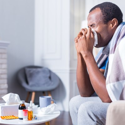 Nice adult man sneezing because he has the flu