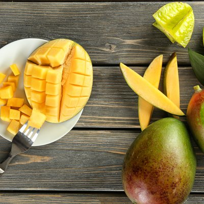 Composition with fresh mango on wooden background