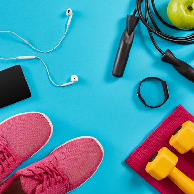 Flat lay shot of sneakers, jumping rope, dumbbells and smartphone on blue background