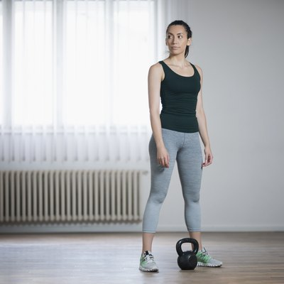 Woman doing at-home strength training workout using a kettlebell