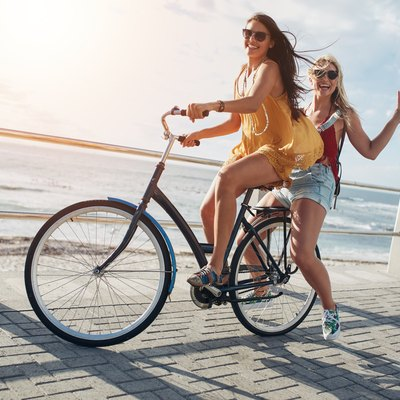 Stylish young female friends on a bicycle