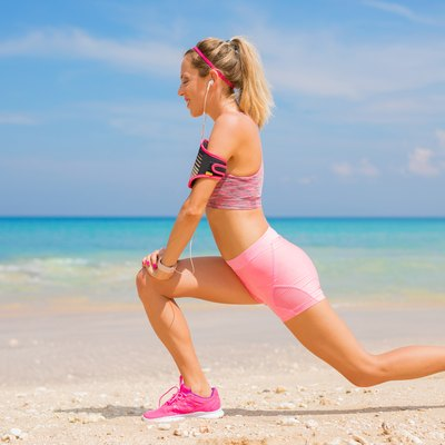 Fitness woman stretching before workout on the beach