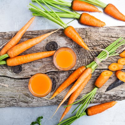 Fresh carrot juice  and raw organic vegetables over rustic wooden table