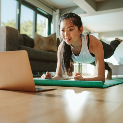 Woman in plank pose following along to a Pilates workout video