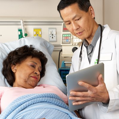 Doctor showing a female patient in a hospital bed a tablet