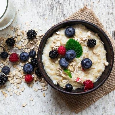 oatmeal porridge with fresh berries, glass of milk and spoon