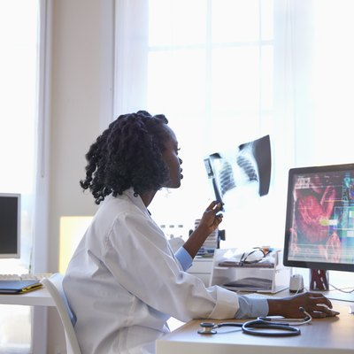 Black doctor examining chest x-ray and using computer