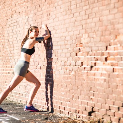 fitness woman stretching the calf on the wall