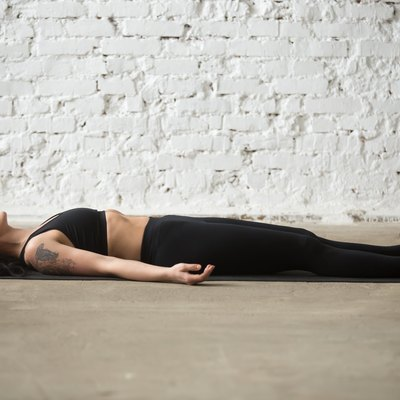 Young yogi attractive woman in Savasana pose, white loft background