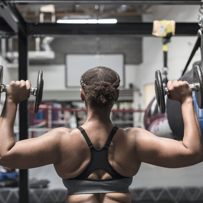 Black woman lifting dumbbells in gymnasium