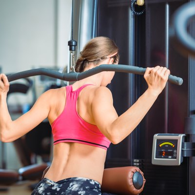 Strong fit woman exercising lat pushdown for back muscles in a modern fitness club