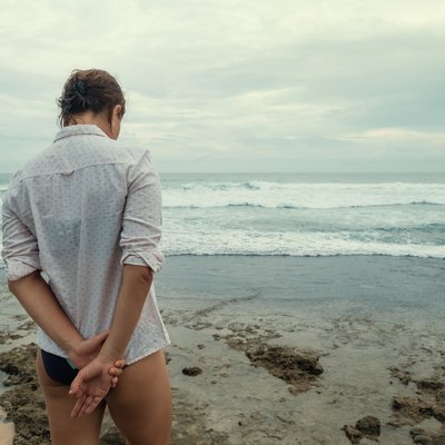 Sad caucasian woman stand on beach. Back view.