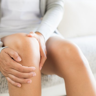 Closeup young woman sitting on sofa and feeling leg pain and she massage her knee at home. Healthcare and medical concept.