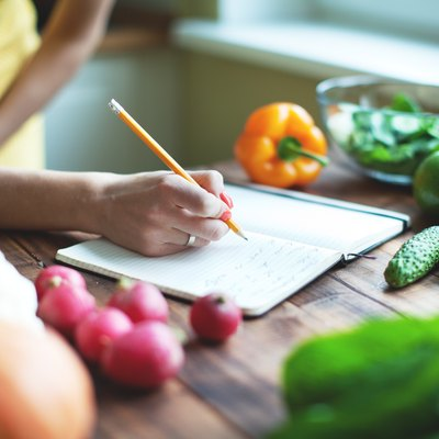 Woman writing meal plan in a journal