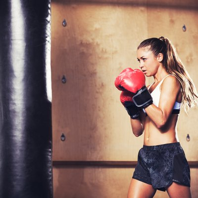 Beautiful fitness woman boxing with red gloves