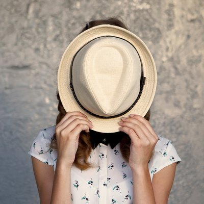 Young girl with hat. Hides her face. Depression.