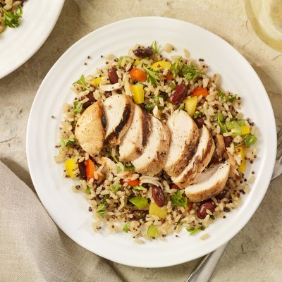 overhead photo of white bowl of grilled chicken with quinoa and brown rice