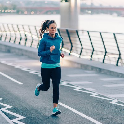 Urban fitness. Woman running by the river