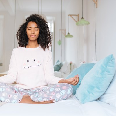 Happy beautiful young black woman relaxed  at home doing morning meditation in bed 'n