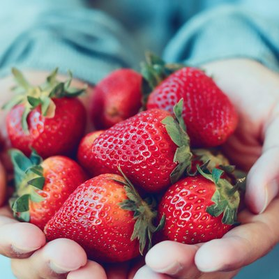 Hands holding a serving of fresh strawberries