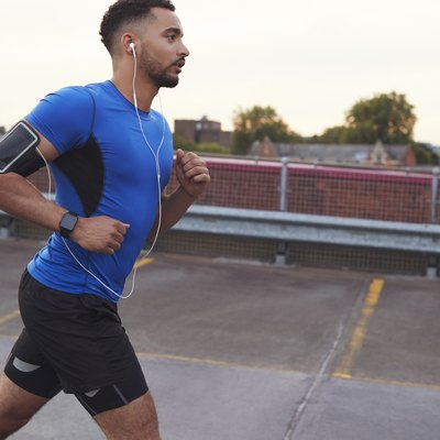 Young male athlete running on a road, side view close up