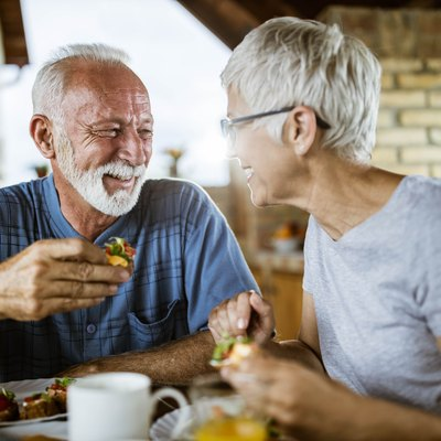 A happy senior couple talking while eating breakfast on a balcony.