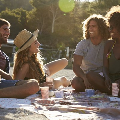 Two couples having a picnic on the beach, backlit