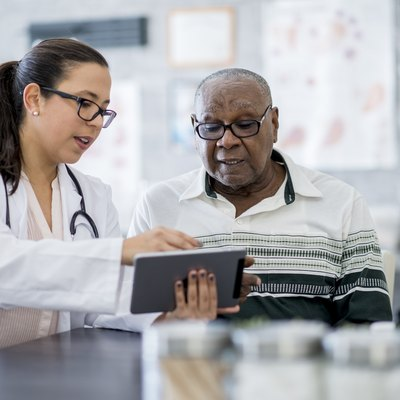 A doctor showing a patient his test results on a tablet computer