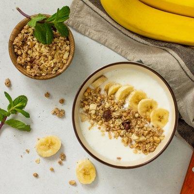 Granola. Granola with yogurt, chocolate and banana on a white stone table.