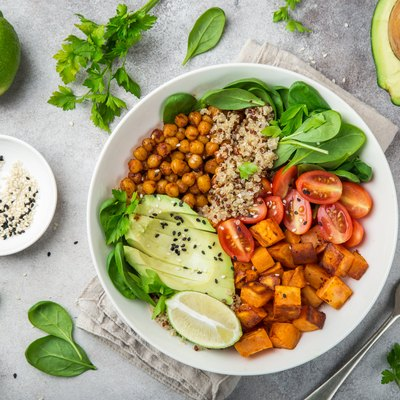 Top view of a bowl of thermic foods, including avocado, quinoa, sweet potato, tomato, spinach and chickpeas