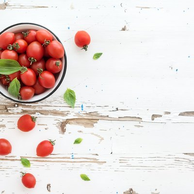 Cherry tomatoes in metal bowl and fresh basil leaves on