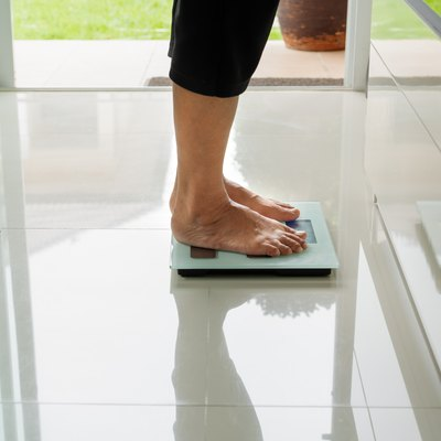 old woman standing on weight scale in living room