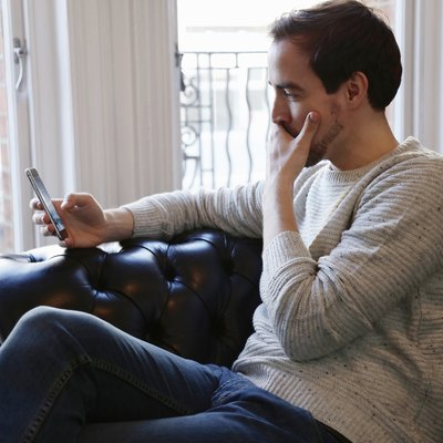 Mid adult man sitting on sofa, looking at smart phone