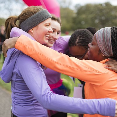 Happy female runners hugging at  charity race finish line, celebrating