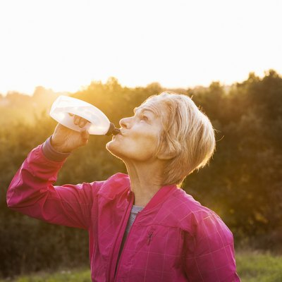 Senior woman drinking water after run outdoors