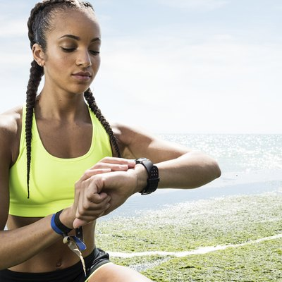 Young woman beside sea, wearing sports clothing, looking at activity tracker