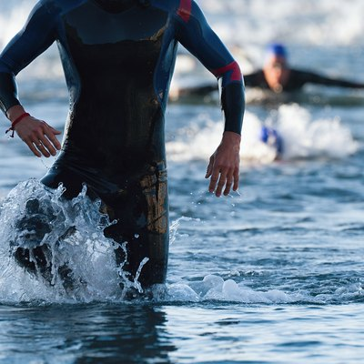 Triathletes running out of the water on triathlon