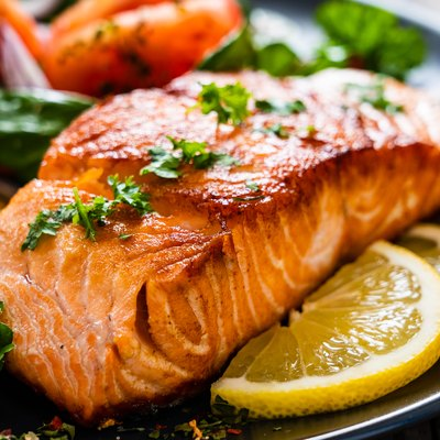 Barbecued protein-rich salmon, fried potatoes, vegetables and lemons on plate