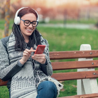 Cheerful woman listening to music in the park