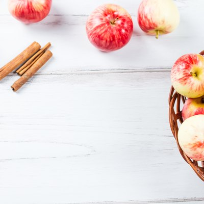 autumn mood composition with red apples in wicker basket and yellow leaves