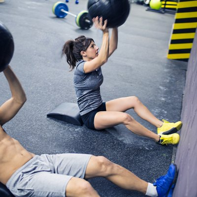 Man and woman doing medicine ball sit-ups during a CrossFit class