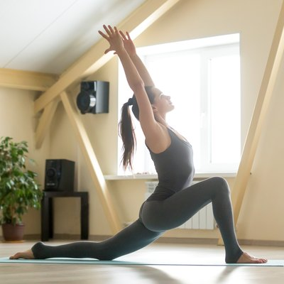 Young attractive woman standing in anjaneyasana pose, home inter