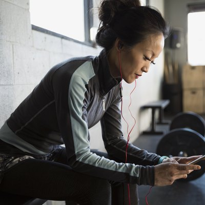 Woman with headphones using cellphone at gym