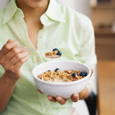 Woman holding bowl of cereal, mid section, close-up