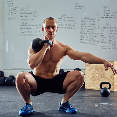 Young athletic man doing kettlebell squat exercise at the gym