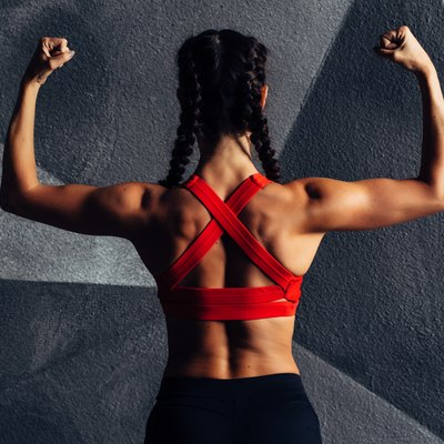 Back view portrait of a fitness woman showing biceps