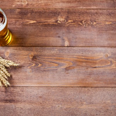 Glass of beer with wheat on a wooden table background with copy space for text. flat lay, top view