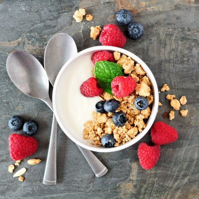 Healthy yogurt with berries and granola, top view over a dark background