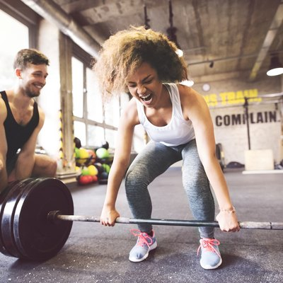 Young woman with training partner preparing to lift barbell in gym